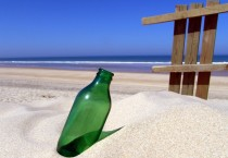 Green Glass Bottle in the Sand at the Beach