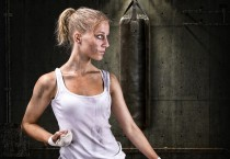 Dirty, Skinny Woman Standing in Front of Heavy Bag